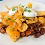 A serving of the frito pie served on a white plate and garnished with sour cream and sliced green onions.