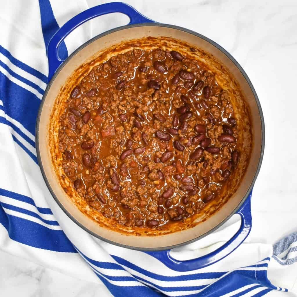 The cooked chili in a blue pot set on a white table with a blue and white striped kitchen towel.
