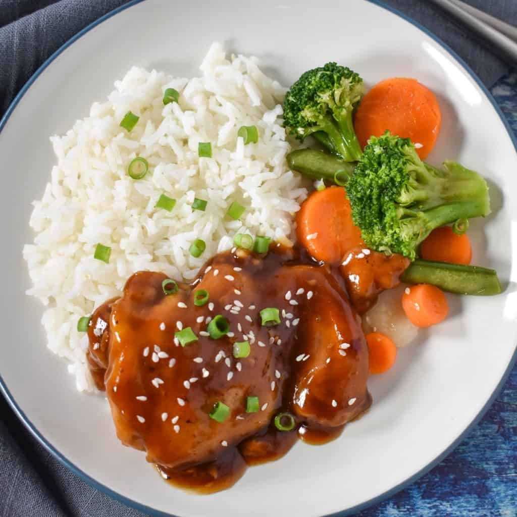 An image of a chicken thigh served with sauce and garnished with sliced green onions and sesame seeds. It is served with white rice and a side of mixed vegetables with broccoli and carrots.