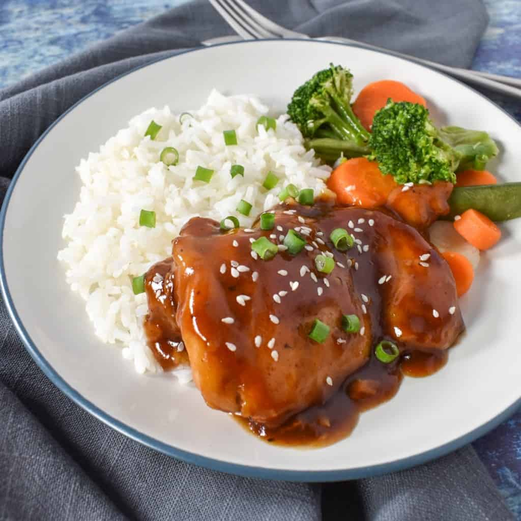 An image of the finished dish served on a white plate with a side of white rice and broccoli and carrots. The chicken and rice are garnished with sliced onions and sesame seeds.