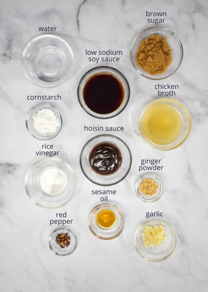 The ingredients for the sauce arranged in glass bowls and set on a white table. Above each ingredient is a label with its name.