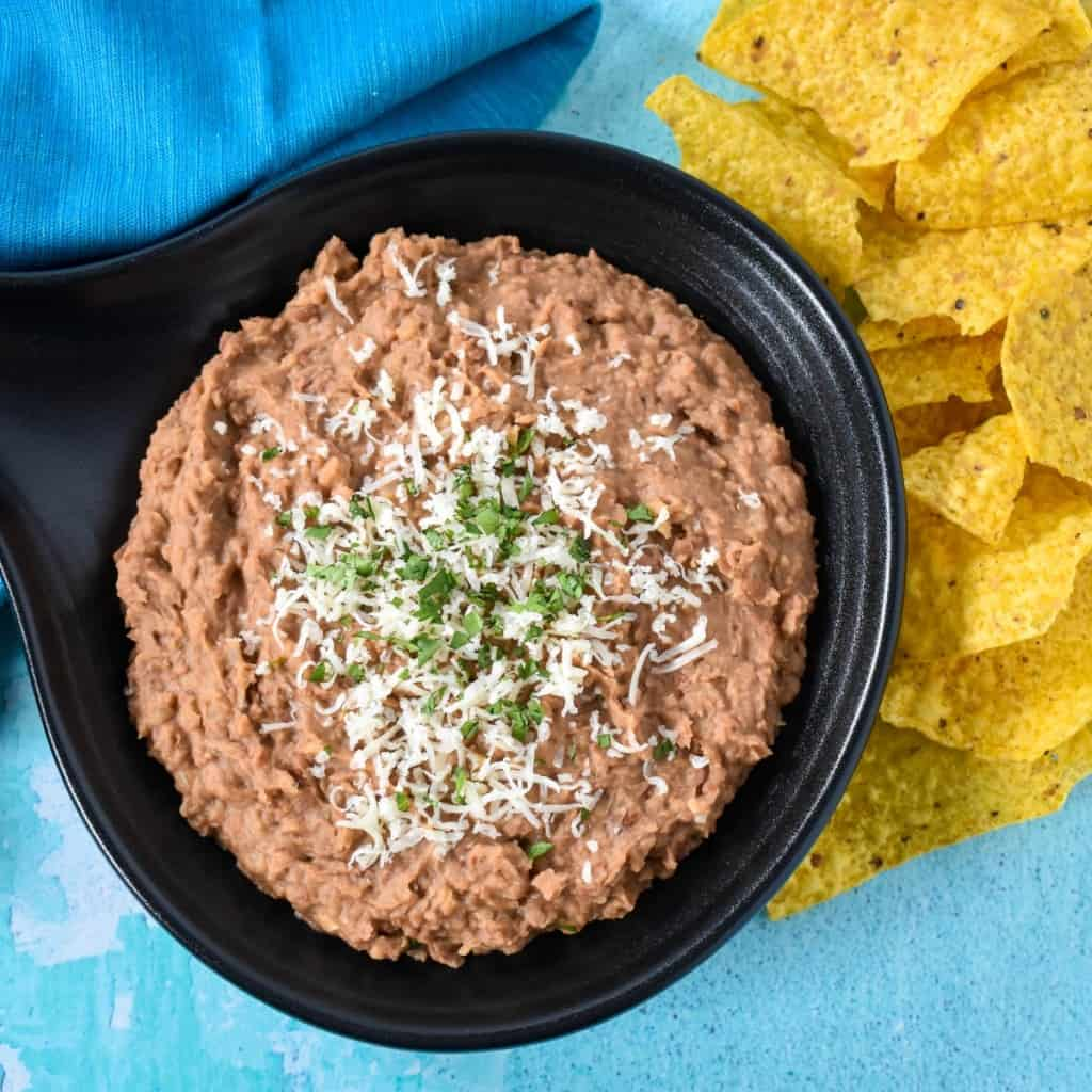 Refried beans served in a black serving skillet with corn tortilla chips to the right and an aqua colored linen set on a light blue board.