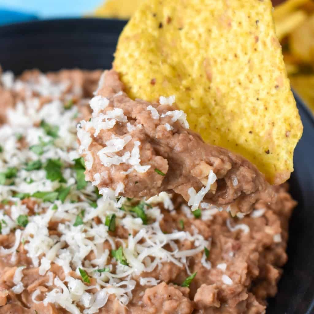 Refried beans garnished with grated cheese and chopped cilantro and being scooped with a corn tortilla chip.