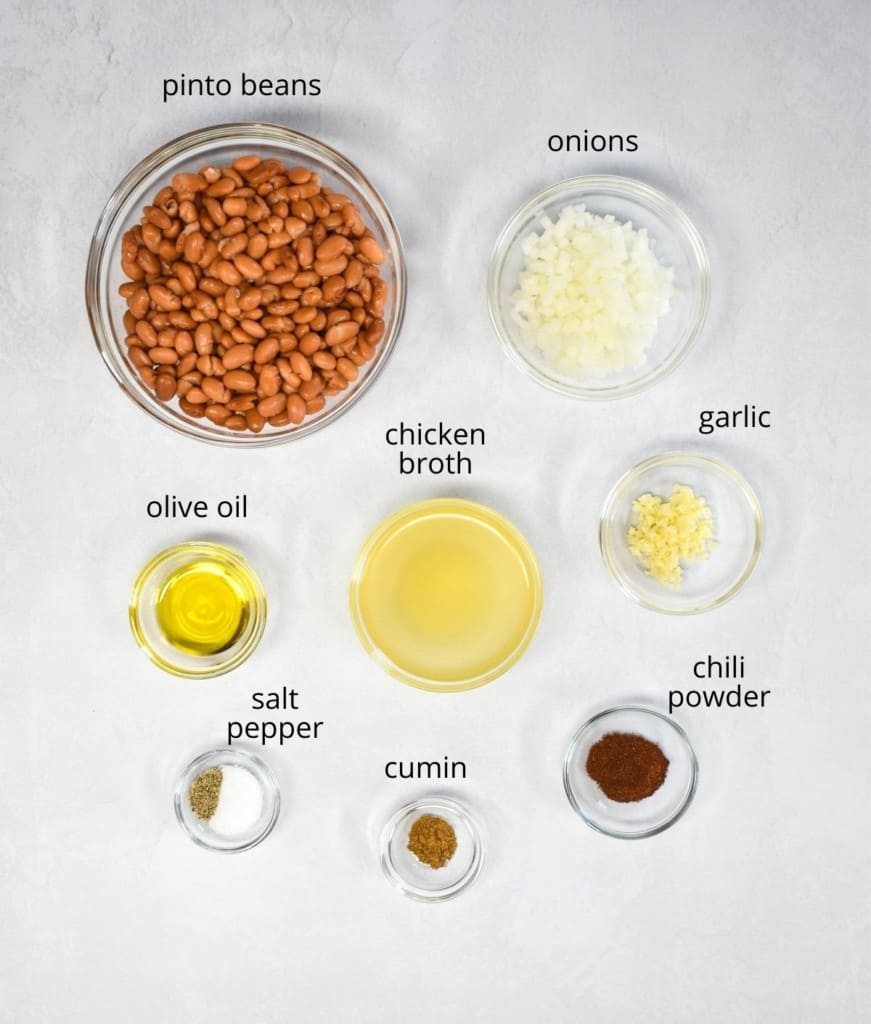 The ingredients for the refried beans, prepped and arranged in clear bowls on a white table.