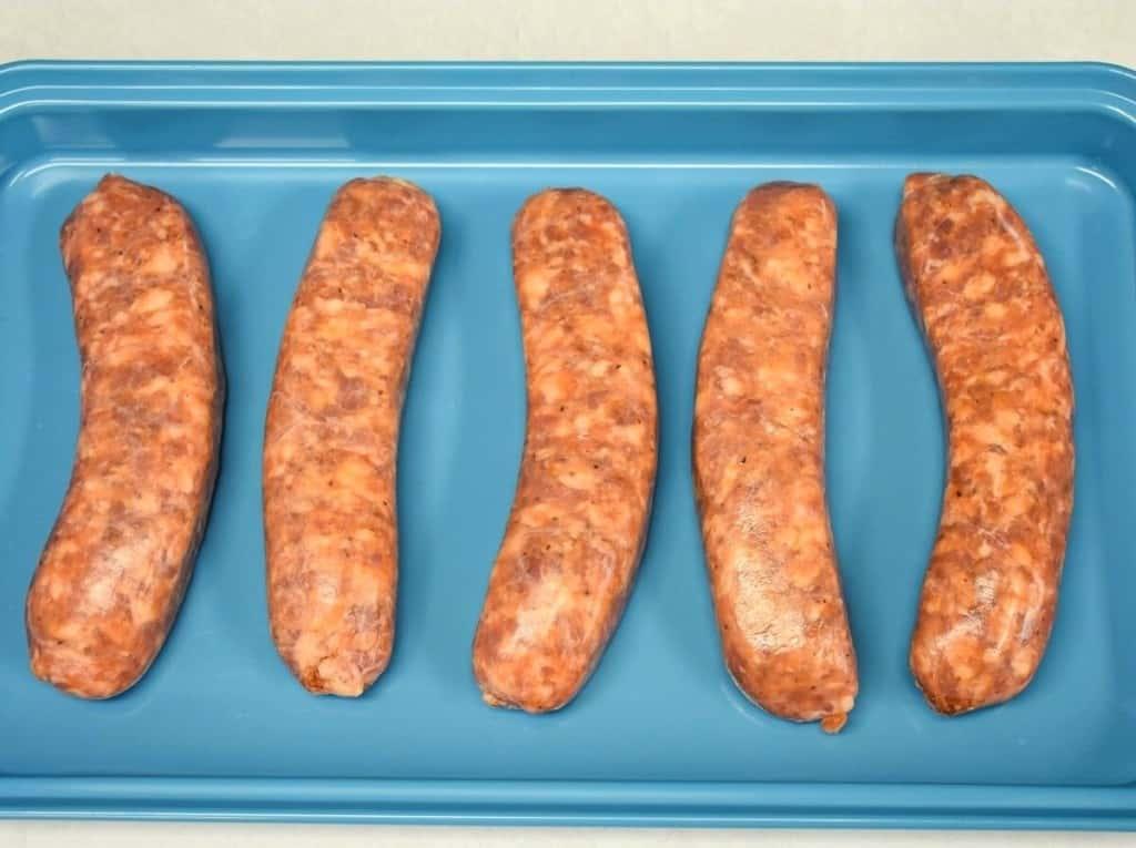 Five Italian sausage links on a light blue pan.