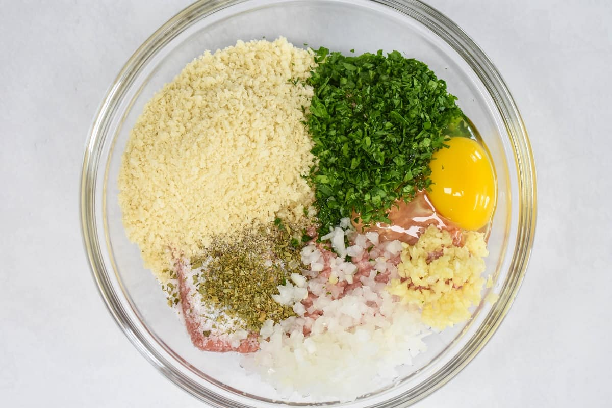 The ingredients for the meatballs in a glass bowl before mixing.