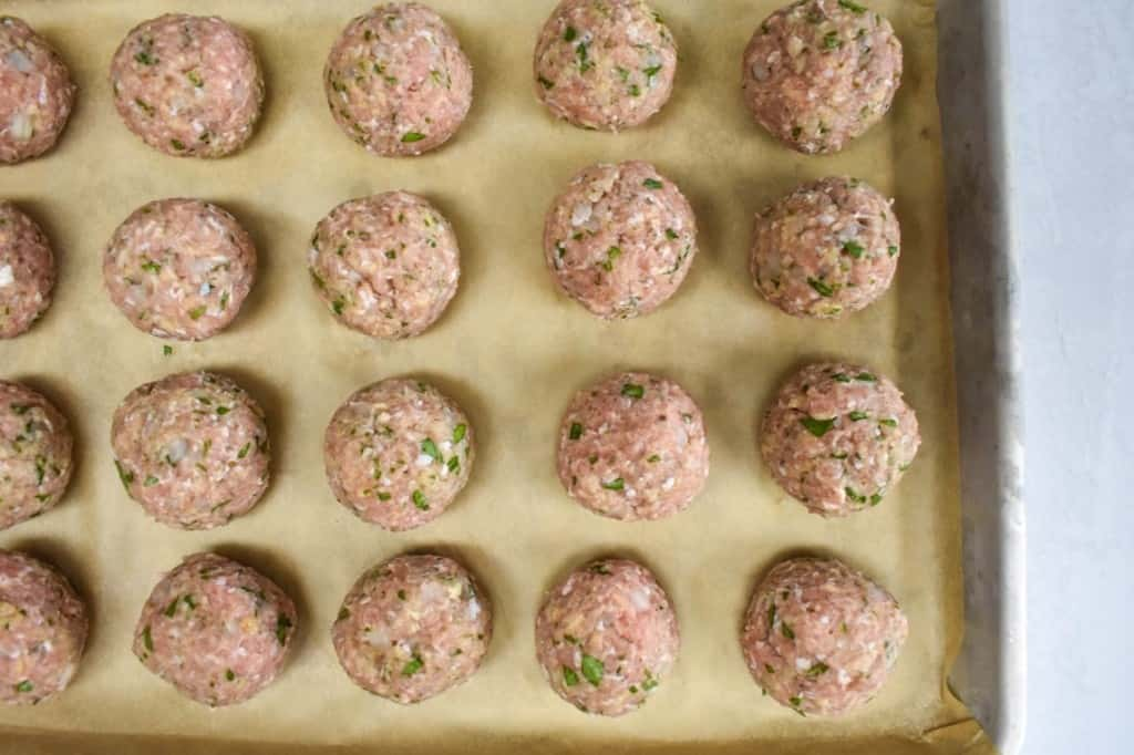 Formed turkey meatballs, before cooking, arranged on a parchment paper lined baking sheet.