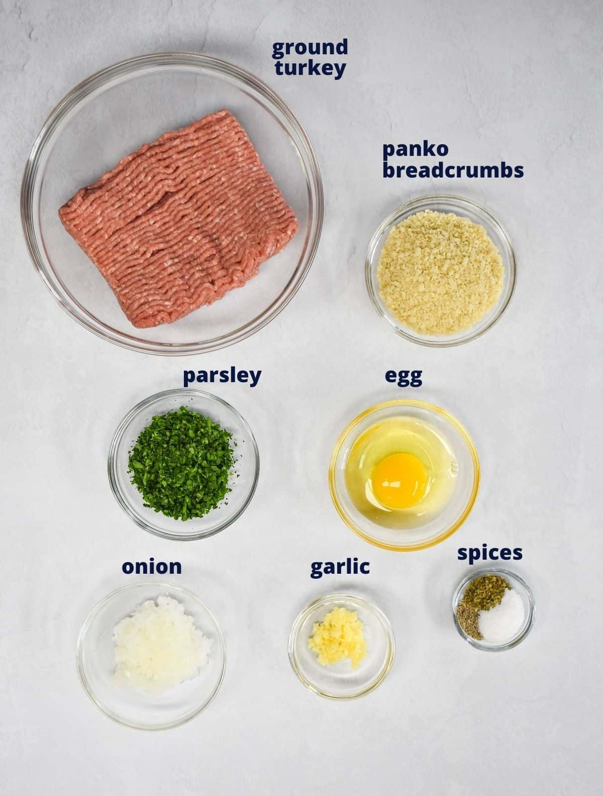 The ingredients for the meatballs prepped and arranged in glass bowls on a white table.