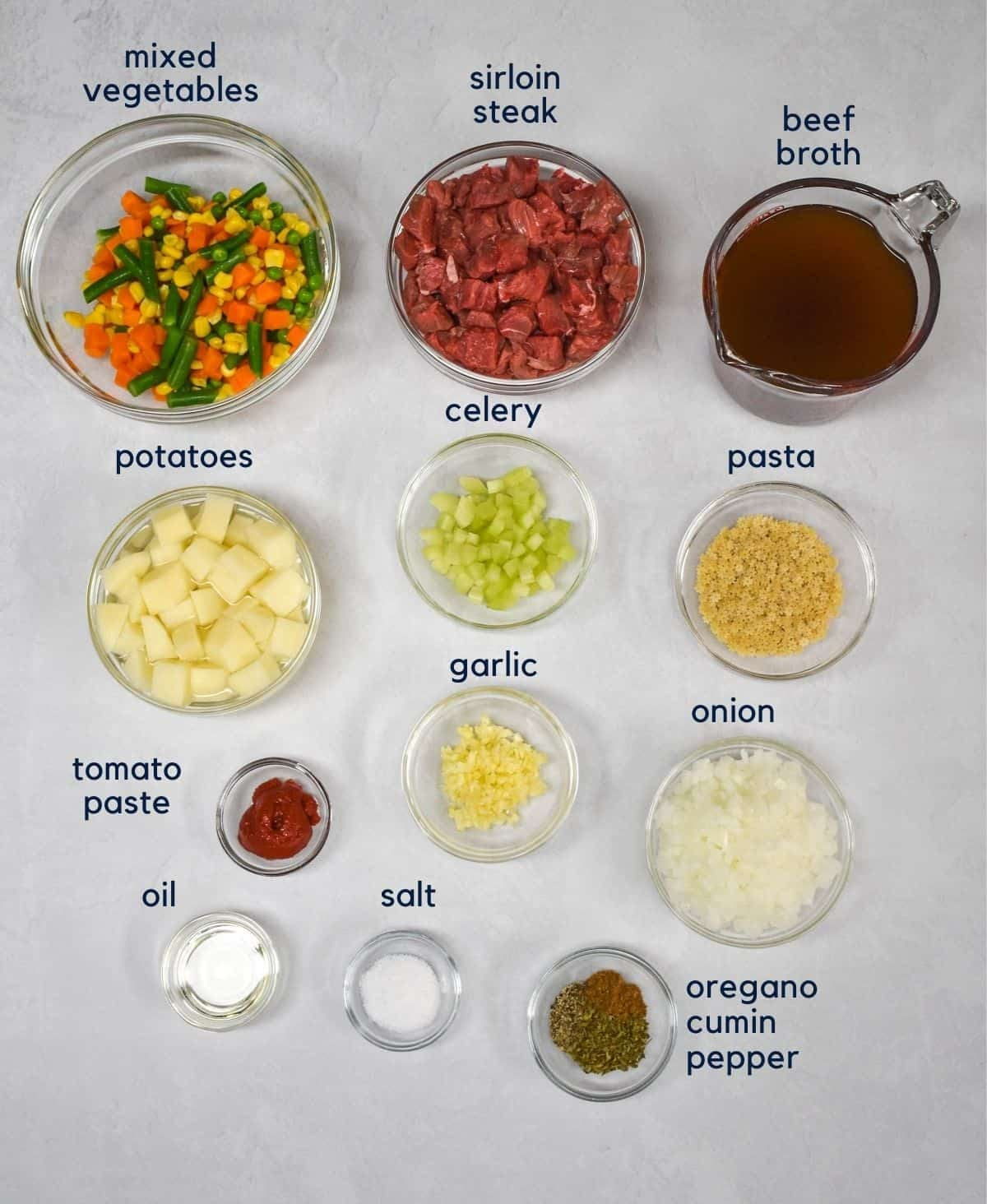 The ingredients for the beef vegetable soup arranged in glass bowls and set on a white table. Each item has a label in small letters above it.