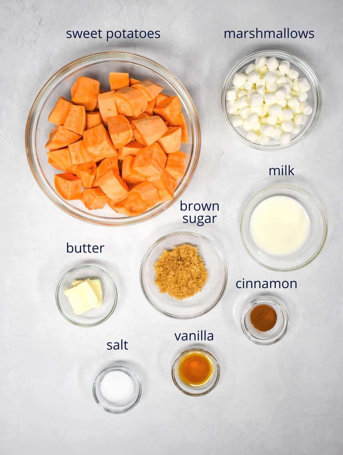 The ingredients for the dish prepped and arranged in glass bowls and set on a white table. Each ingredient has a small label with its name.