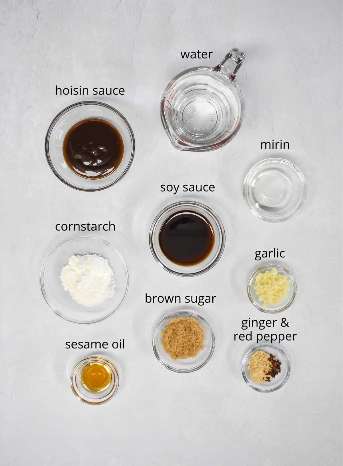 The ingredients for the sauce arranged in glass bowls and set on a white table. Each ingredient has a small label with the name in black letters.