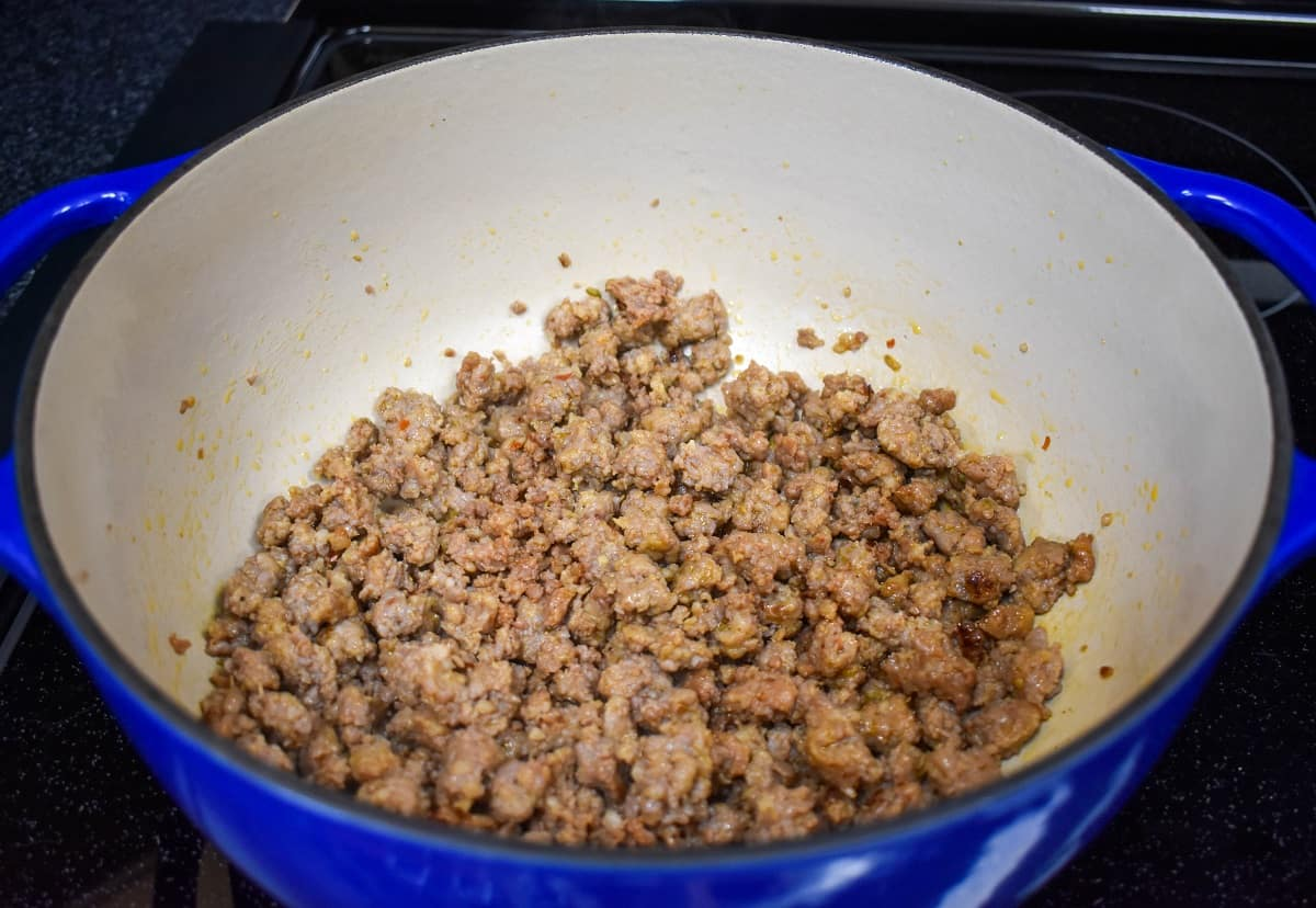 An image of browned crumbled sausage in a large pot that is off-white on the inside and blue on the outside.