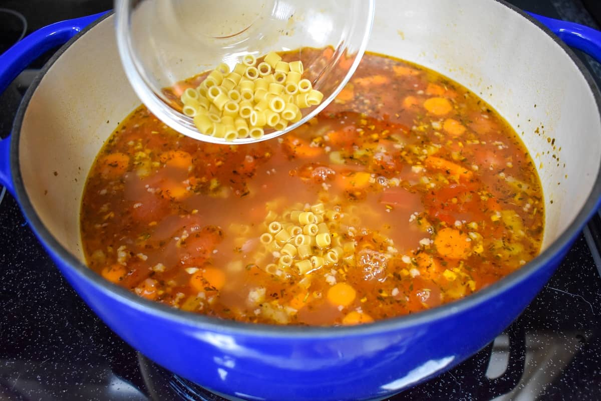 An image of small pasta being added to the pot.